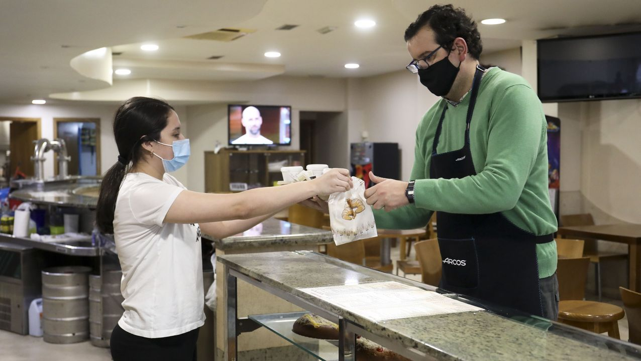 Diana Viéitez, de la cafetería Che de Sigüeiro, entrega unos cafés para llevar a Diego Veiga, de la carnicería Jesus Veiga