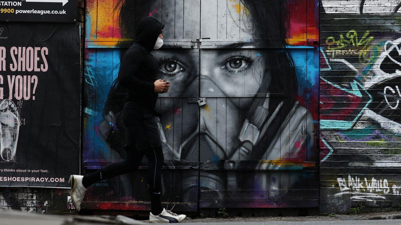 Un hombre con una máscara protectora corre por delante de un graffiti en Brick Lane, en Londres