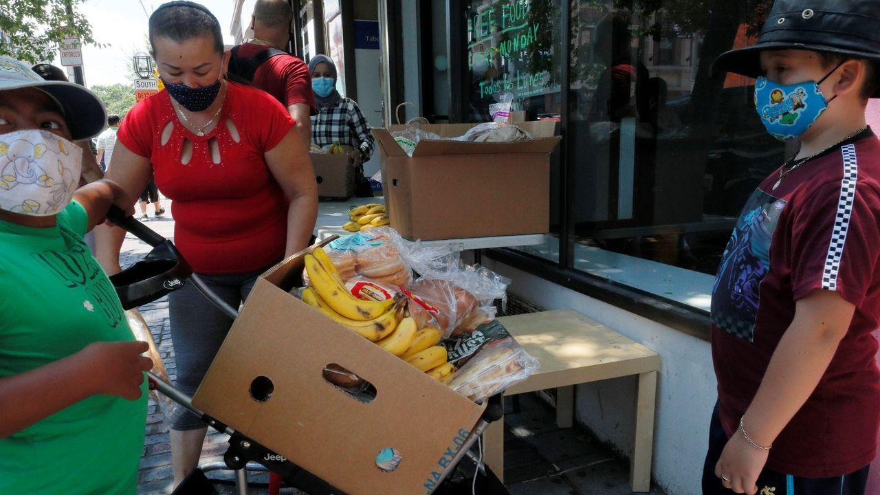 Una mujer recoge alimentos distribuidos por el Centro Internacional de Avivamiento en Chelsea, Estados Unidos