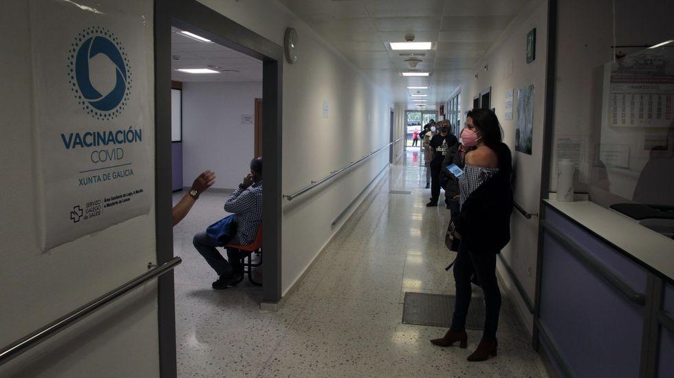 Una mujer muestra su hombro a una enfermera antes de recibir la vacuna esta mañana en el hospital de Monforte
