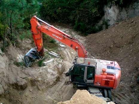 Una máquina excavadora junto a los restos del castro.