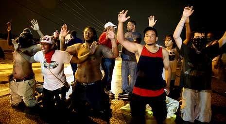 Jóvenes de Ferguson levantan las manos ante la policía, en recuerdo al gesto que hizo Michael Brown antes de ser abatido por un agente.