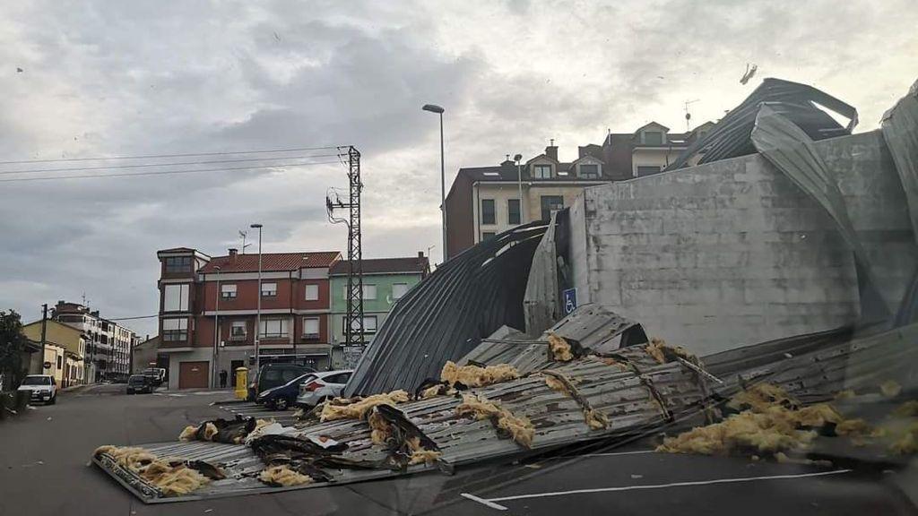 La borrasca «Karim» desploma el techo del polideportivo de El Berrón.Varias personas caminan por el paseo de la playa de San Lorenzo de Gijón