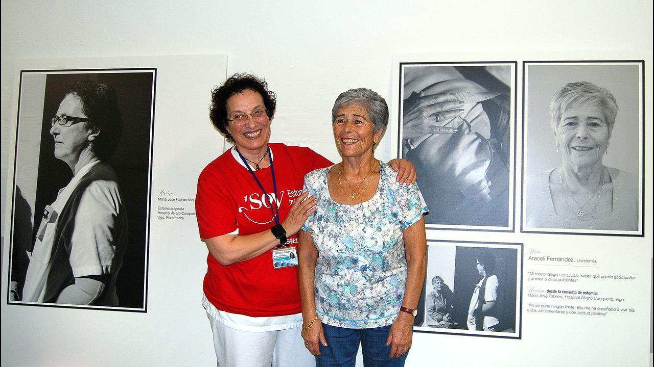 La enfermera María José Fabeiro y la paciente Araceli Fernández, delante de los paneles de la exposición del HAC que muestran sus fotos.