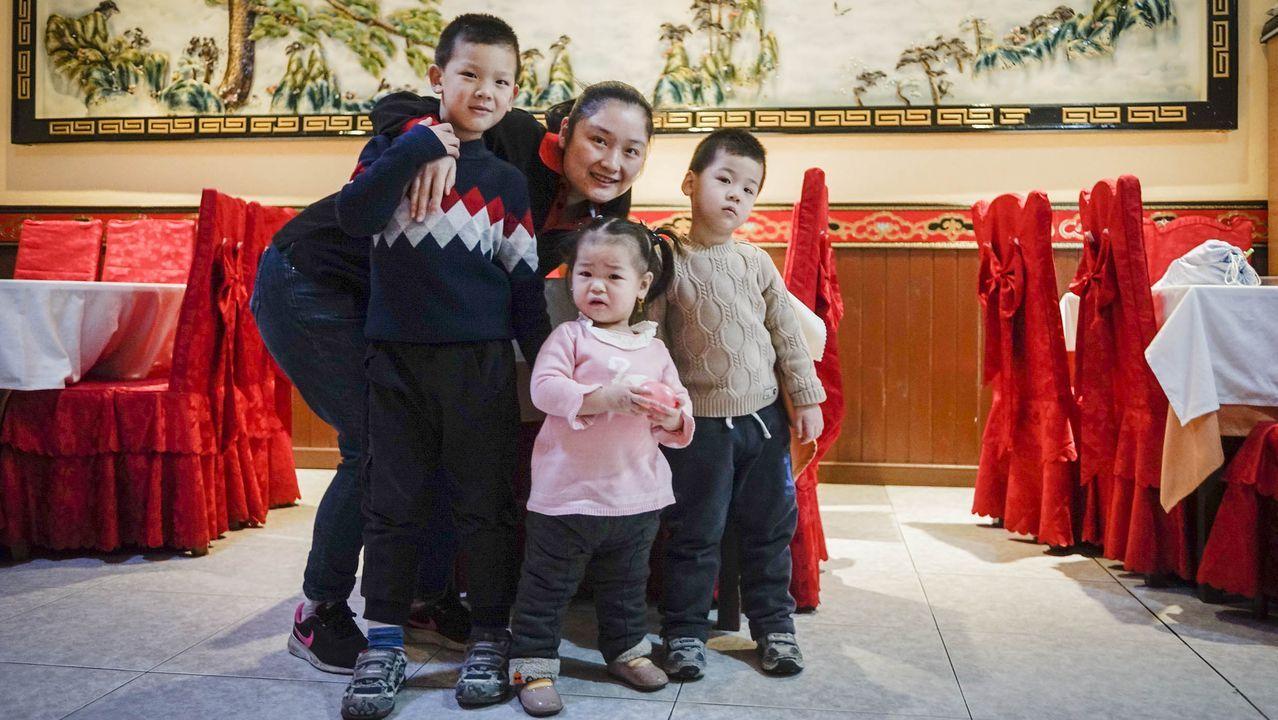 Weilian Xia, junto a sus tres hijos, en el restaurante donde trabaja
