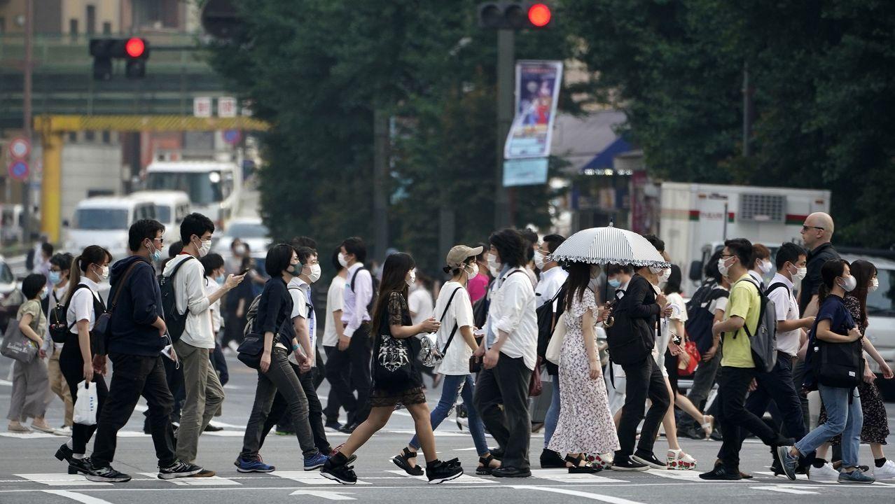 Los peatones con máscaras cruzan una calle en el distrito de Akihabara en Tokio, Japón