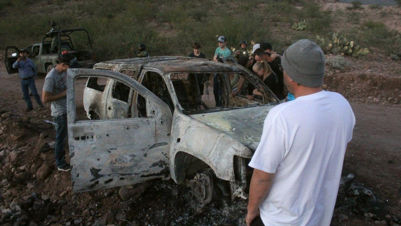 Miembros de la familia LeBarón observan el vehículo calcinado donde fueron asesinados sus familiares cuando circulaban por las comunidades de Bavispe y Ejido Pancho Villa