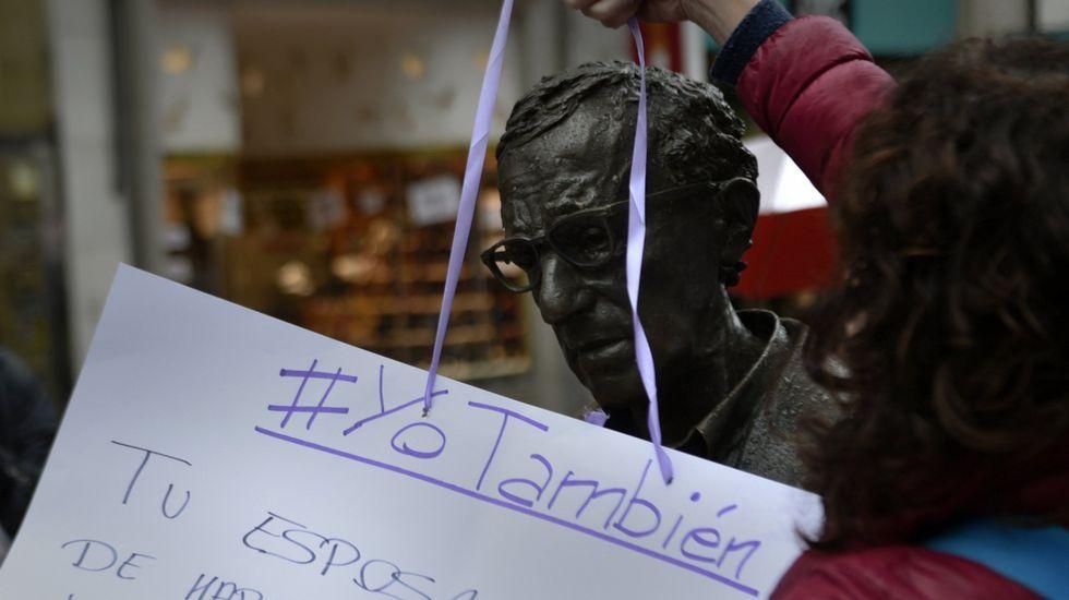 Varios grupos de turistas se sacan fotos con la estatua de Woody Allen, en Oviedo.Un cartel con acusaciones contra Woody Allen cuelga durante una manifestación contra la violencia de género