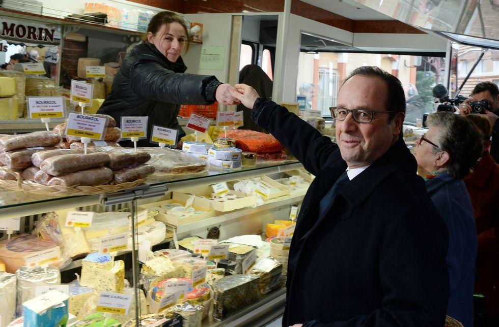 Hollande estrecha la mano de una vendedora en la visita a un mercado ayer en Tulle.