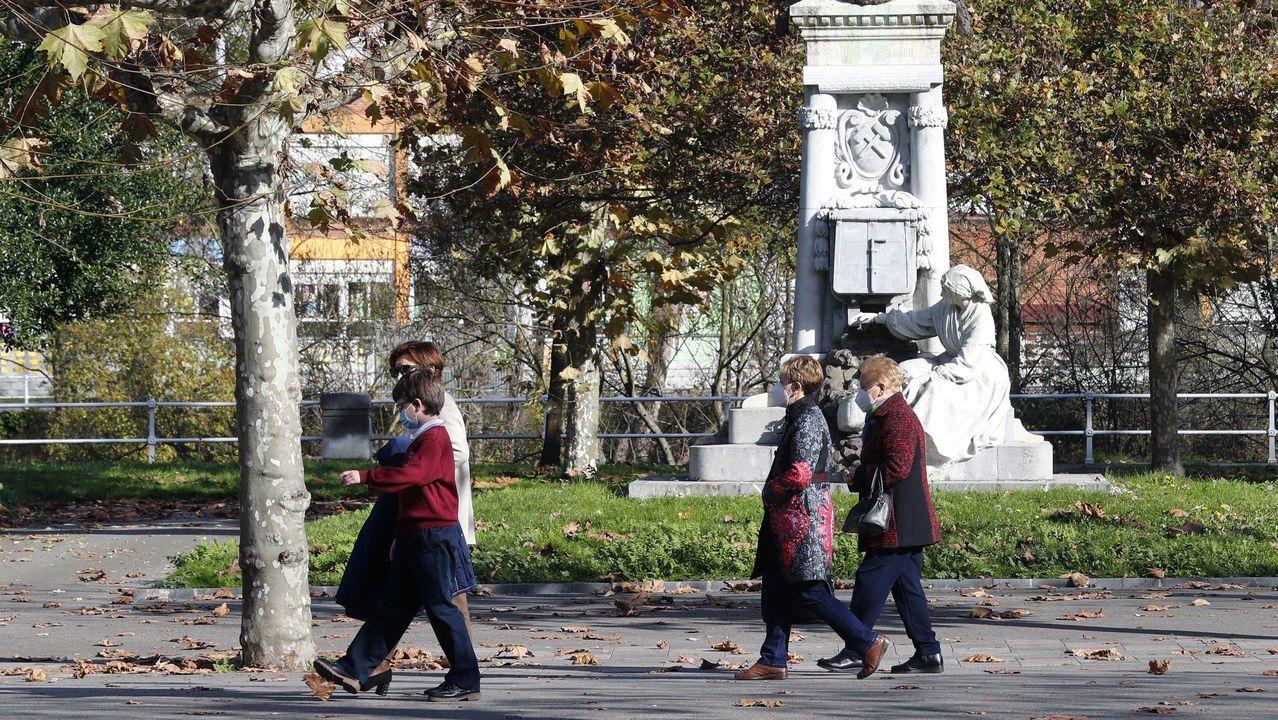 Varias personas caminan este lunes en un parque de Sama de Langreo
