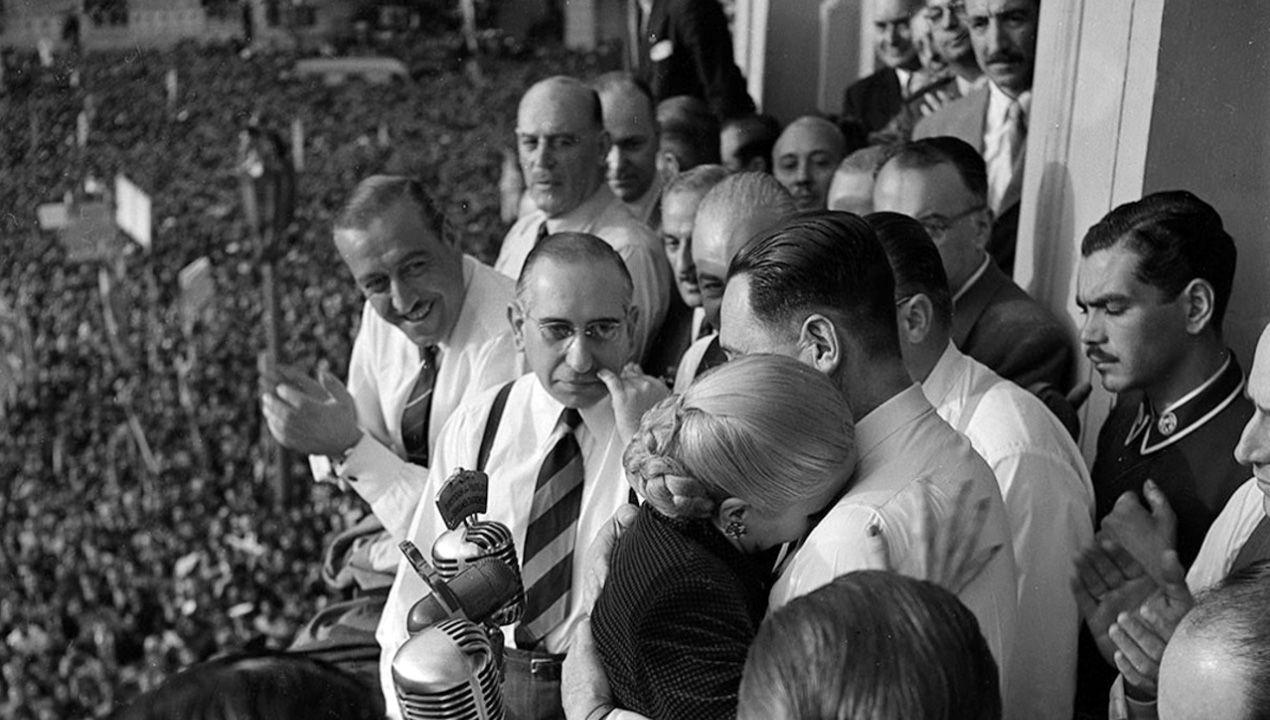 Eva Duarte de Perón, Evita, se abraza a Juan Domingo Perón durante la celebración sindical de 17 de octubre de 1950. En este palco estaba el sindicalista asturiano Isaías Santín, que recibió una medalla