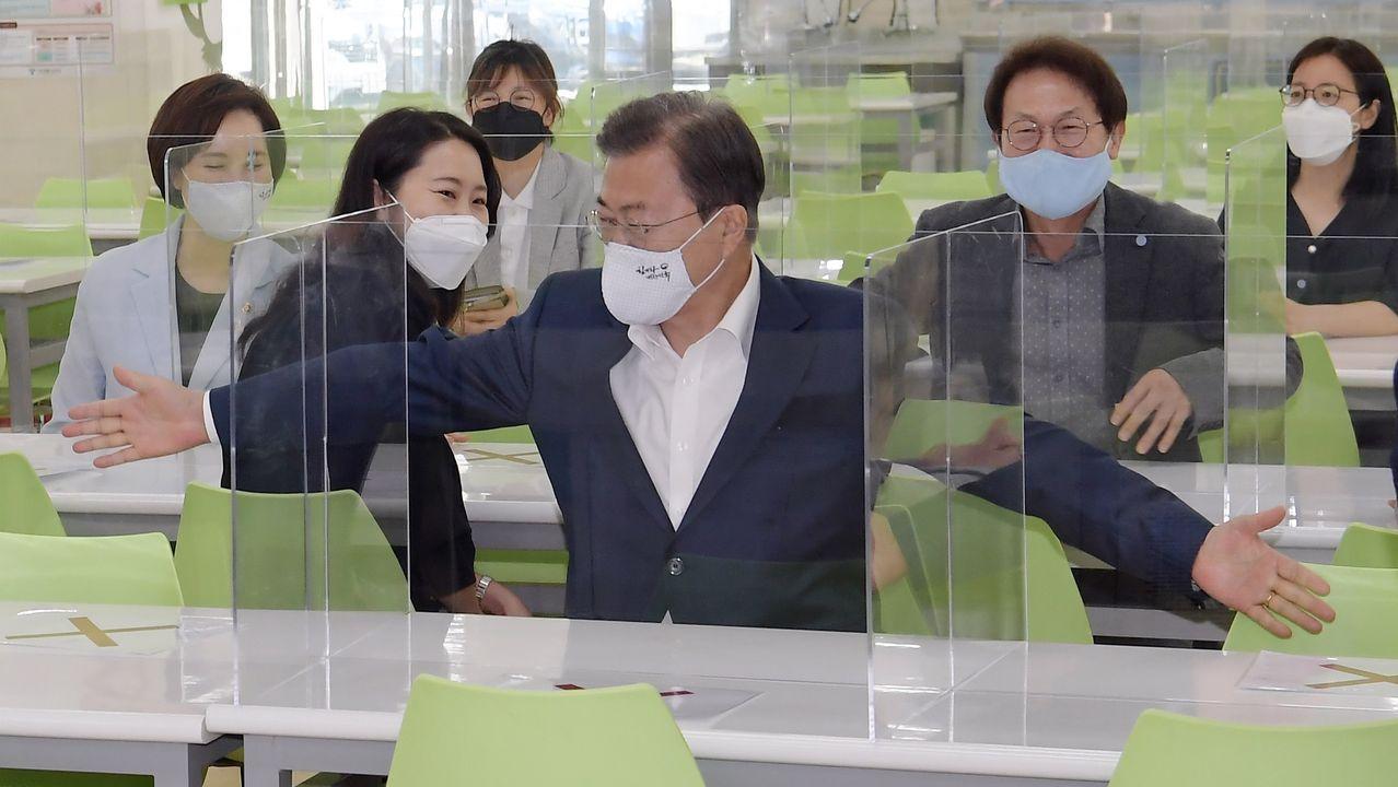 El presidente de Corea del Sur, Moon Jae-in, extiende los brazos para medir la distancia entre los asientos en la cafetería de una escuela de Seúl. Los colegios reabrirán la próxima semana
