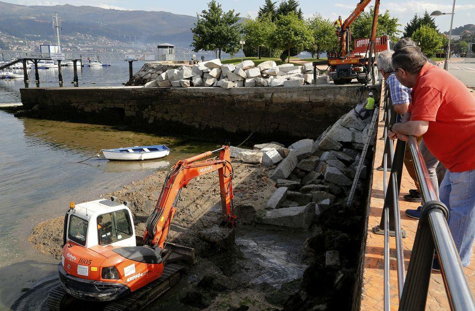 Un vehículo oruga coloca los bloques de granito para evitar embate de las olas.