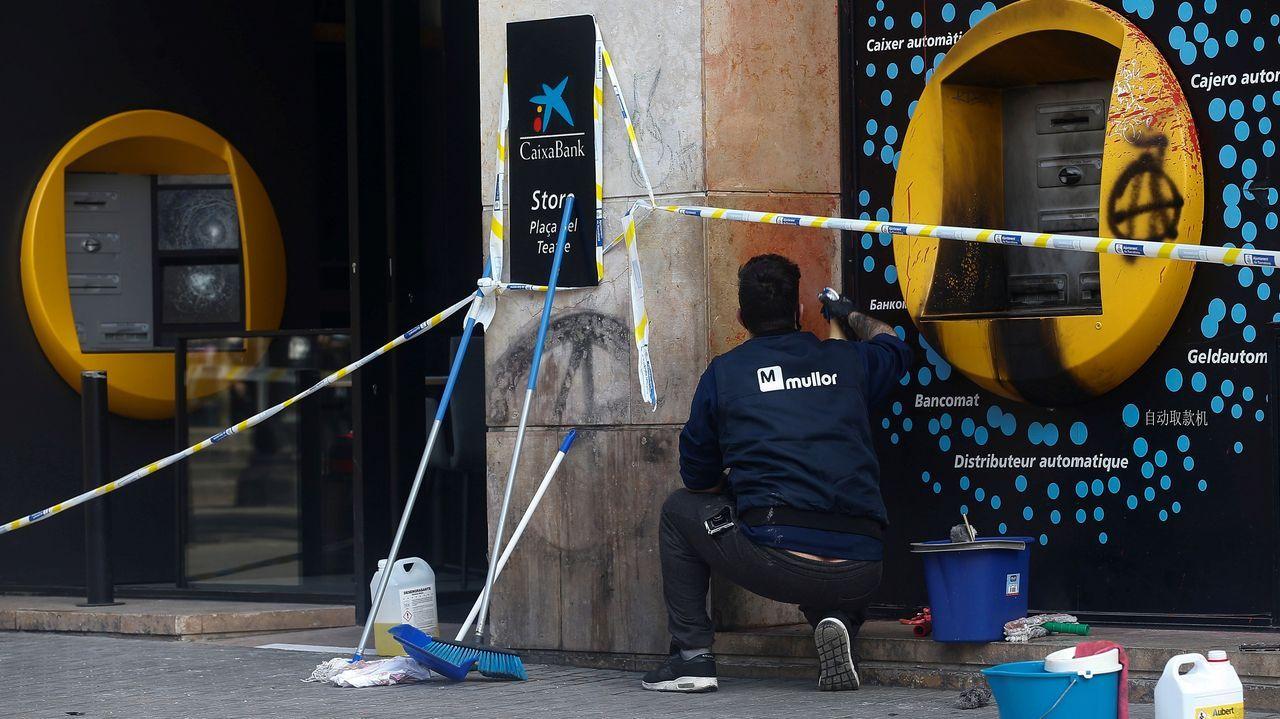 Un operario intenta arreglar los daños causados en una oficina bancaria durante los disturbios en Barcelona