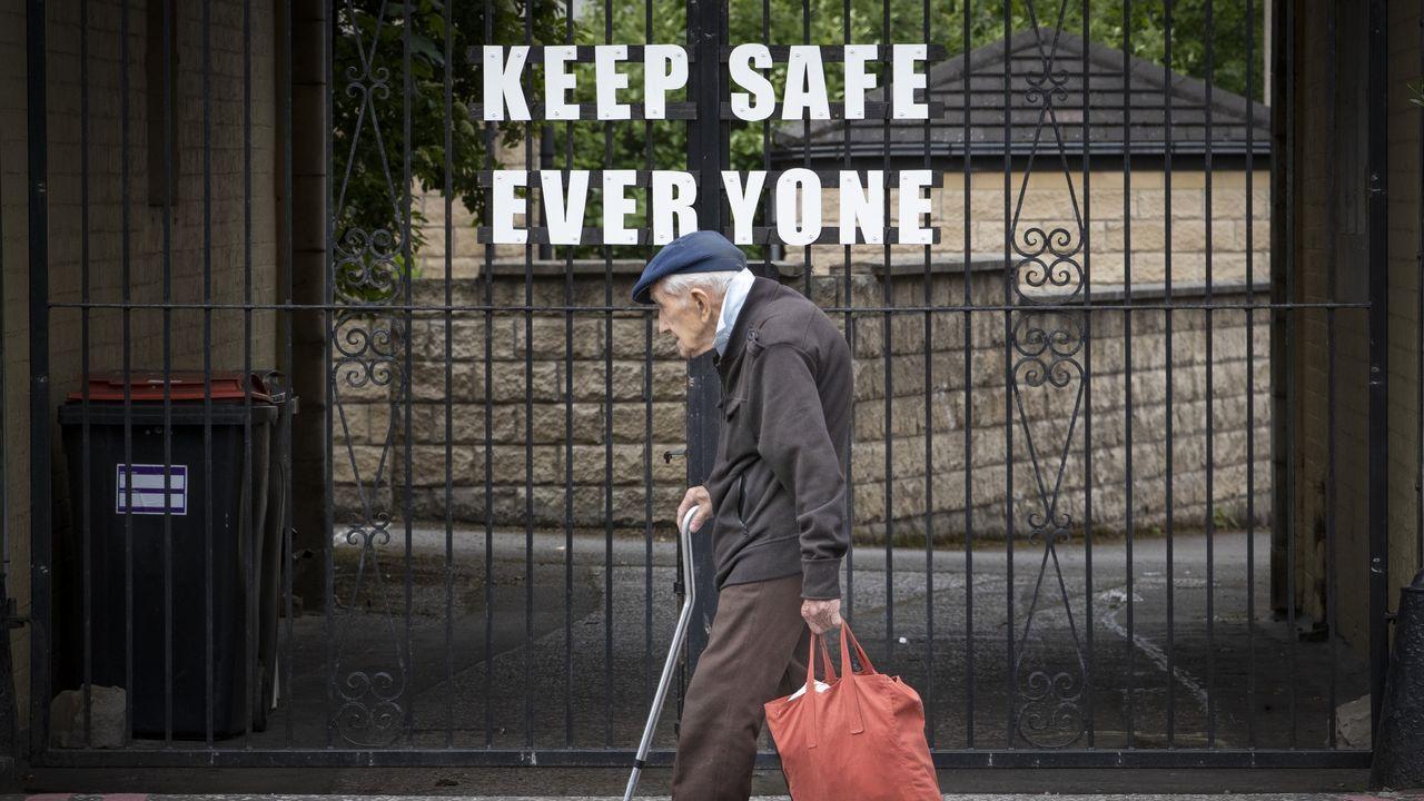 Un anciano pasa por delante de la puerta de un parque escocés cerrado en el que se puede leer «manténganse todos a salvo»