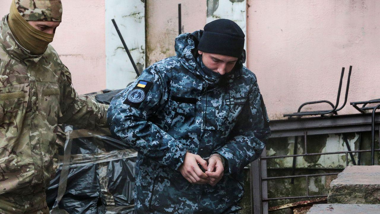 Putin abre la puerta a un posible conflicto nuclear.Un agente del servicio secreto traslada a uno de los marinos ucranianos al tribunal de Sumferopol
