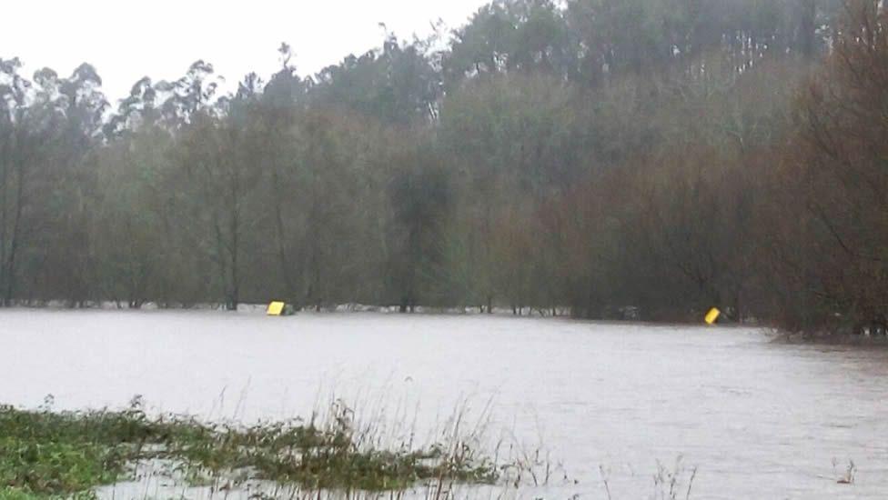 Carretera cortada y área recreativa inundada en la playa fluvial de Tapia (Ames)