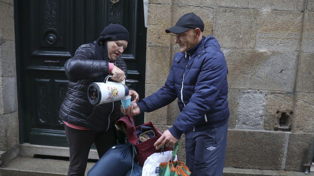 En medio de la calle, ofreciendo un chocolate caliente a una de las personas a las que ayuda normalmente