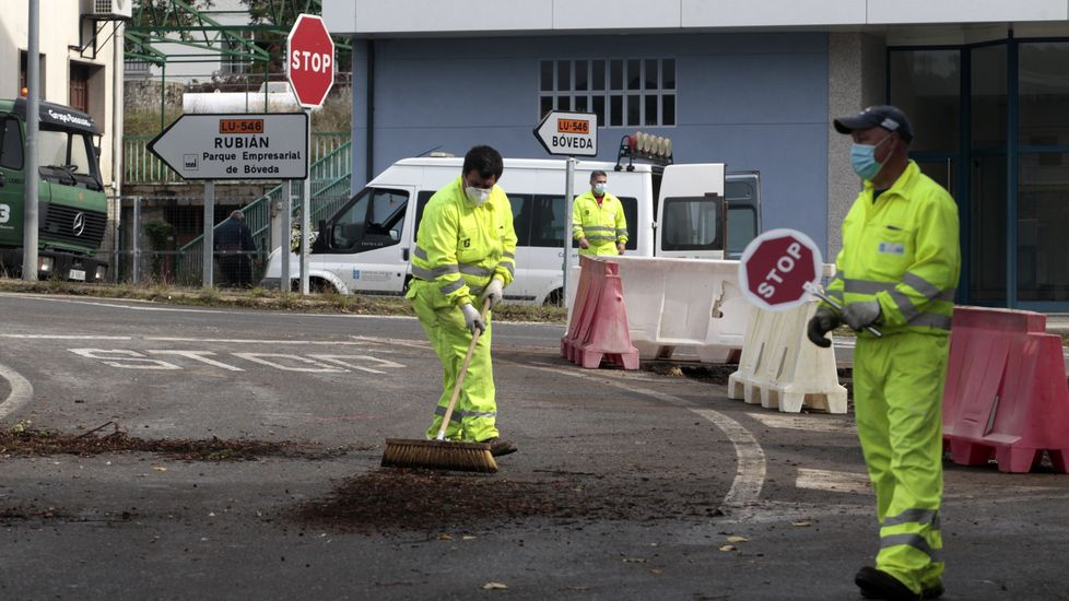 Un obrero limpia la calzada al final del turno de mañana de la primera jornada de trabajo en el cruce de Bóveda