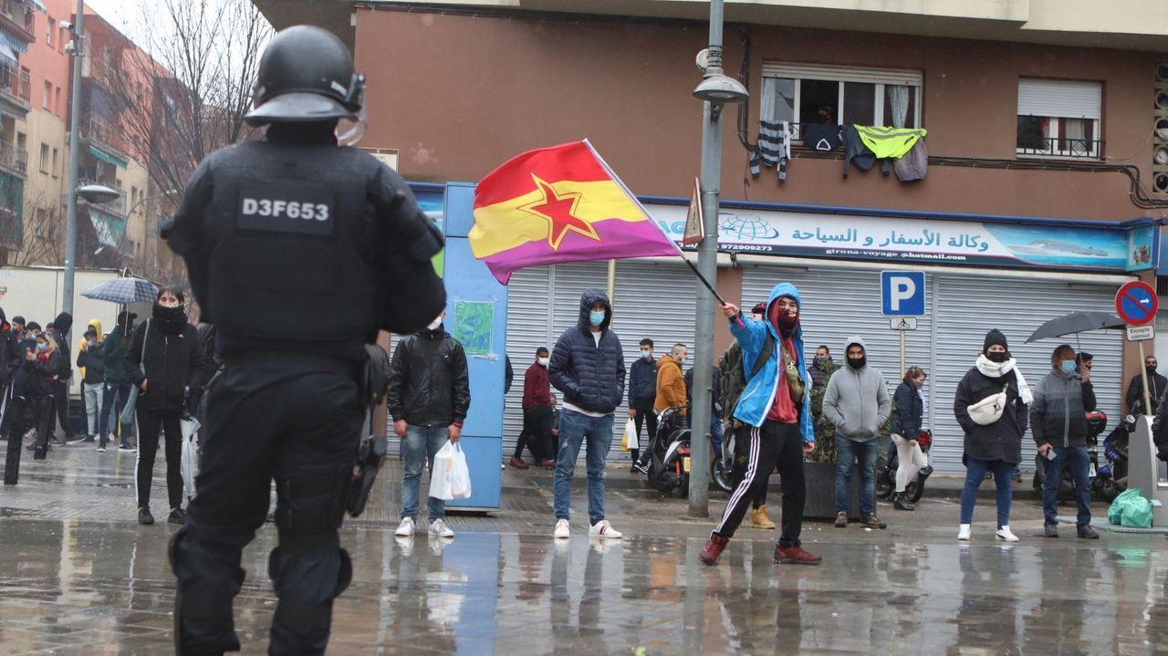 Un agente antidisturbios de los Mossos frente a los manifestantes que llevan banderas republicanas en Salt (Gerona) tras un mitin del líder de Vox, Santiago Abascal