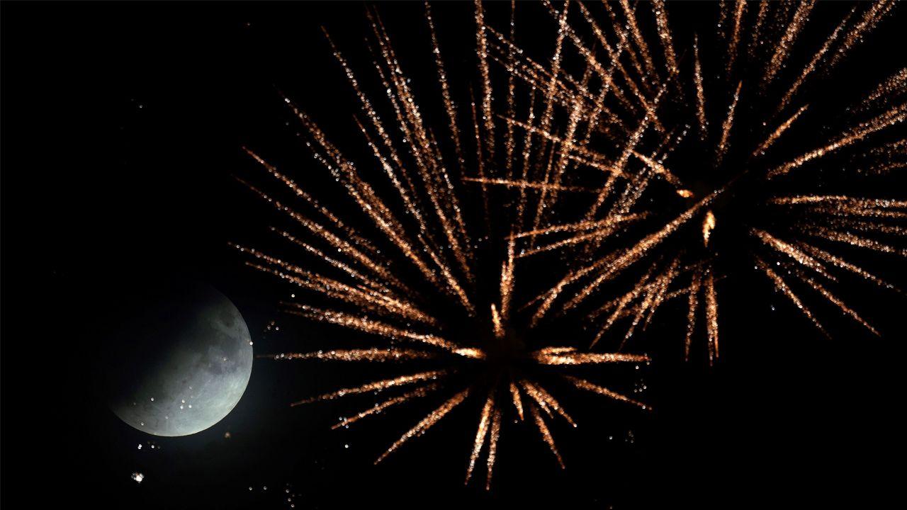 La luna parcial sobresale entre los fuegos artificiales en el festival Brezel, en la localidad alemana de Speyer