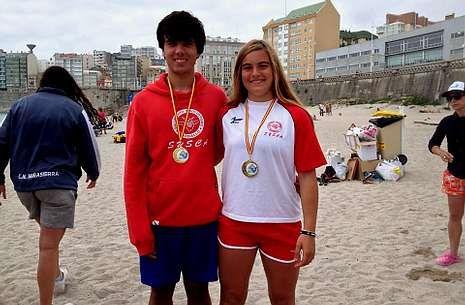 Valeria Gómez Anido y Adrián Martínez Cotelo posan con sus medallas en la playa del Orzán.