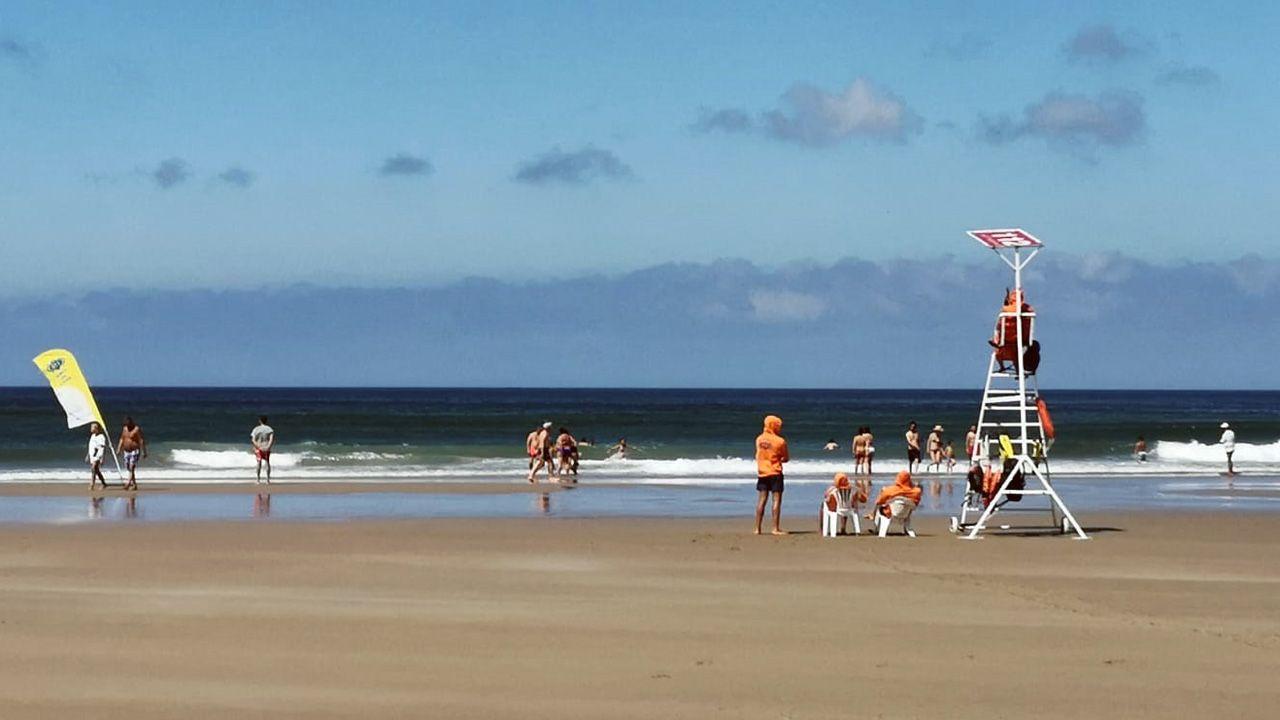 El otoño será más cálido de lo normal en Galicia.Bañistas y el equipo de salvamento en la playa de Xagó
