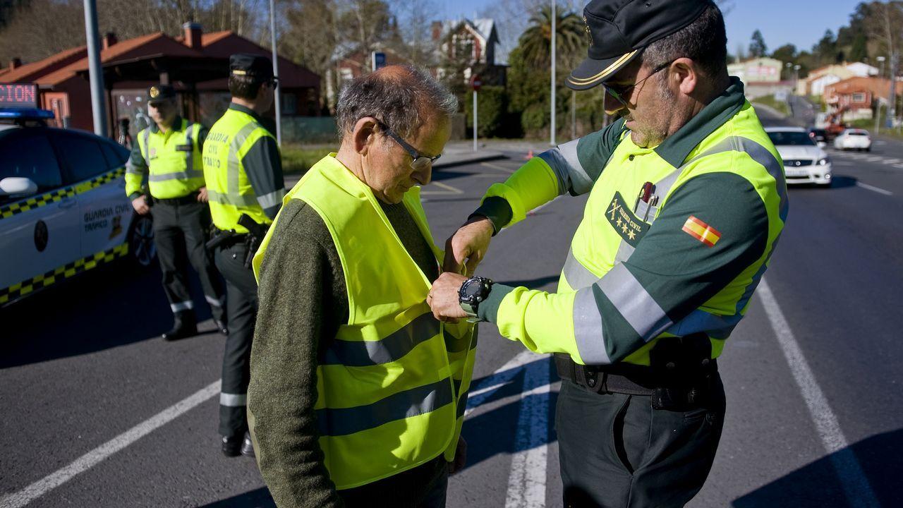 El #TopVacacional de la DGT: hospital, cárcel o cementerio.LA GUARDIA CIVIL REPARTE CHALECOS. El capitán de la Guardia Civil de Tráfico de A Coruña ayuda a un peatón a ponerse el chaleco