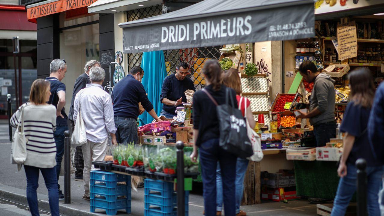 El mundo toma distancias.Cola de clientes ante una frutería en París