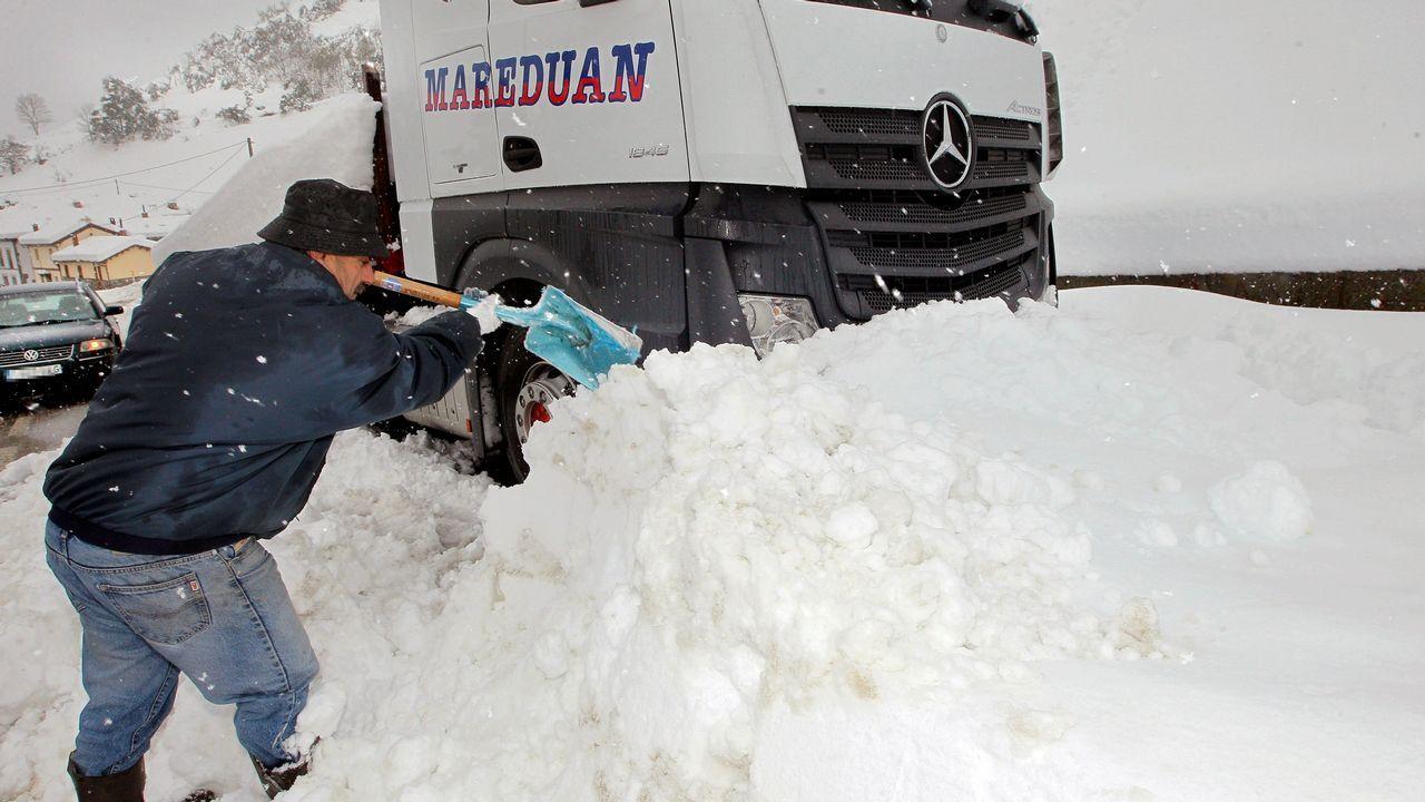 Un camionero trata de desploquear su camión de la nieve, en el pueblo de Pajares