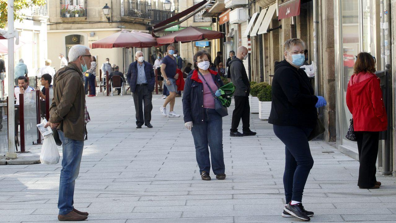 Gente con mascarillas hace cola en la calle Cardenal