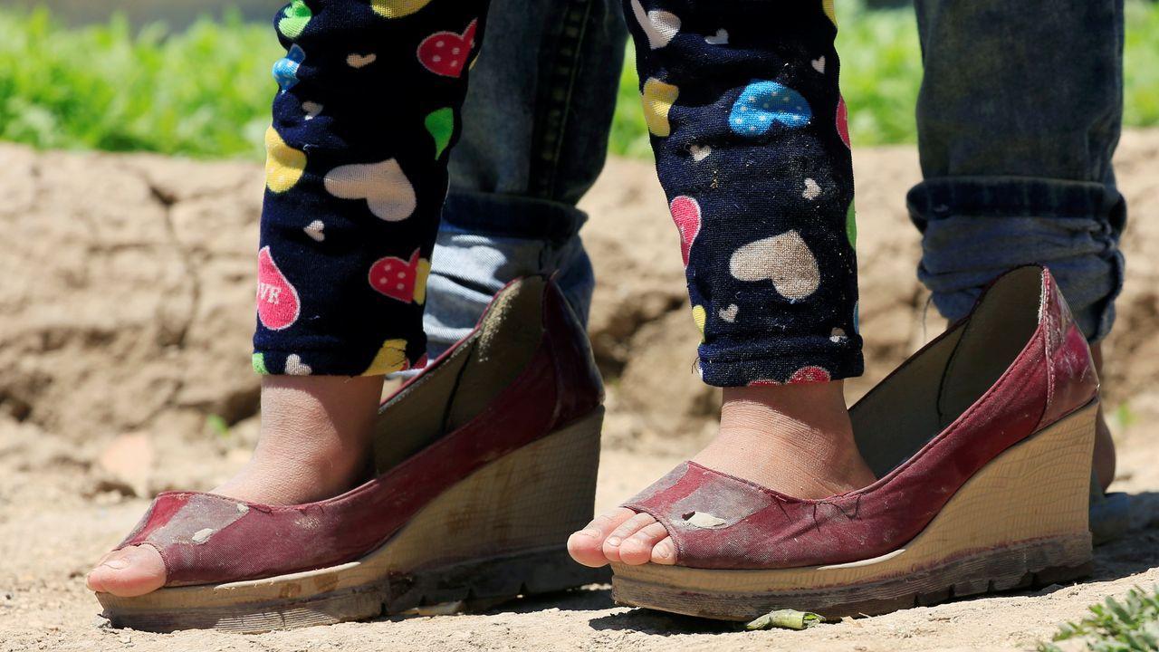 En Líbano, una niña refugiada de la guerra de Siria viste unos zapatos de adulto. Allí, al drama del día a día han sumado el coronavirus