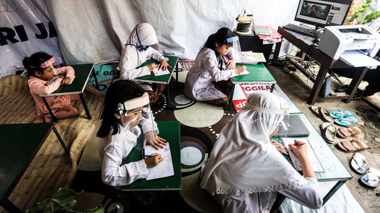 Estudiantes utilizan mascarilla mientras que reciben clases virtuales en Bandung, Indonesia
