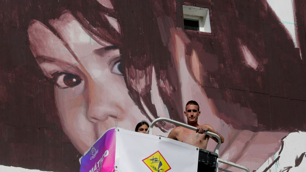 Las fachadas de Cambre cobran vida.Slim Safont, trabajando en una pared de la rúa Amil.