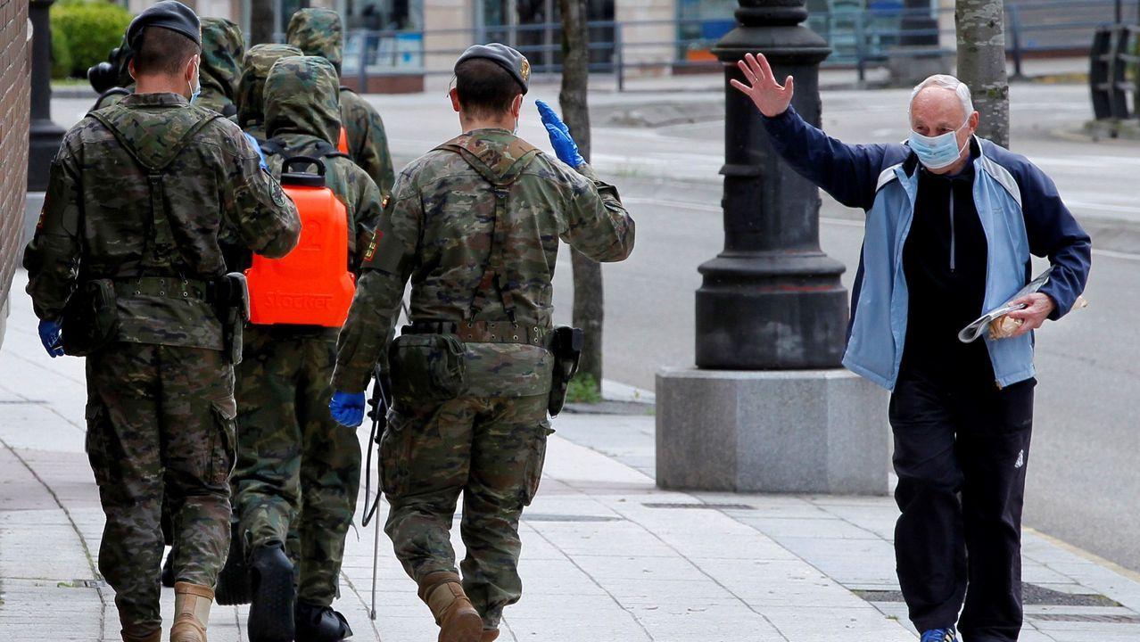 Un ciudadano vitorea a varios soldados que trabajan en la desinfección de la ciudad, este domingo, en Oviedo,