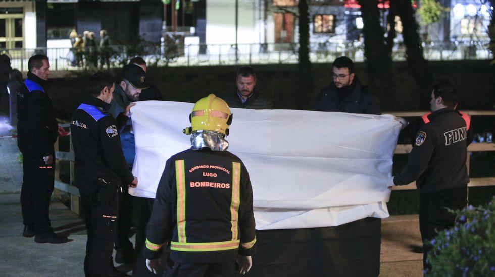 Bomberos y policías junto al cuerpo, tapado con una sábana mientras lo examina la médico forense