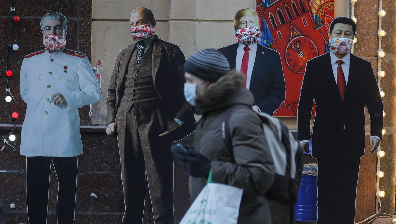 Un hombre pasa junto a tres figuras de cartón del ex líder soviético  Lenin (i), el presidente estadounidense, Donald Trump (c), y el presidente chino, Xi Jinping, cubiertos con máscaras faciales en una tienda de recuerdos en Moscú (Rusia). Mañana miércoles los comunistas rusos homenajearán a Lenin