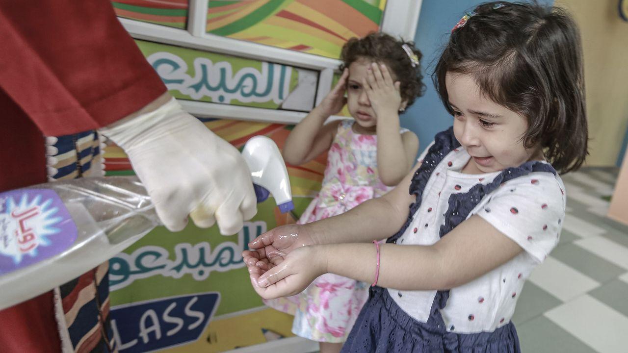 En Gaza, una mujer palestina rocía desinfectante en las manos de unas niñas, una vez que se ha decretado la reapertura de algunos comercios y espacios públicos