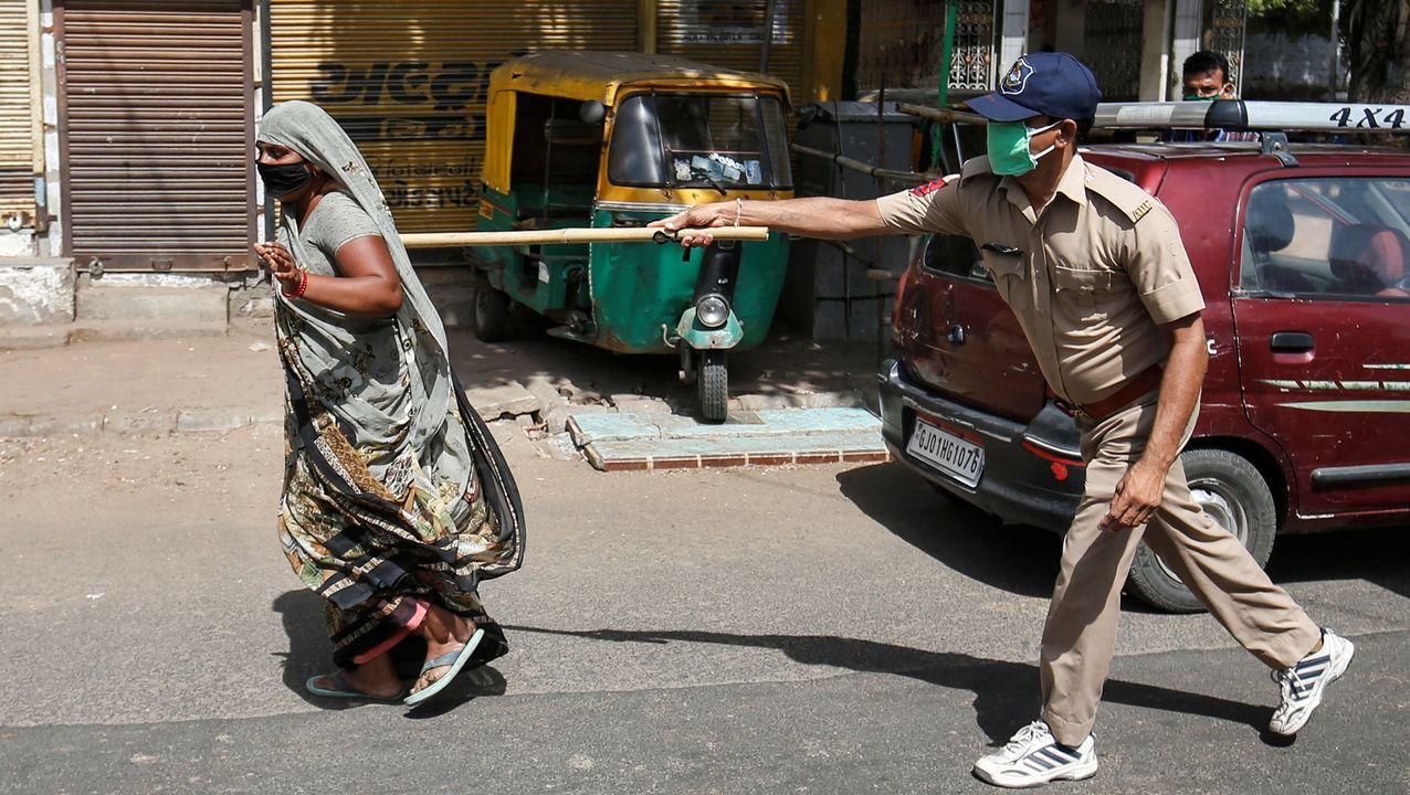 Un policía usa su bastón para presionar a una residente que infringe las reglas en una ciudad de La India