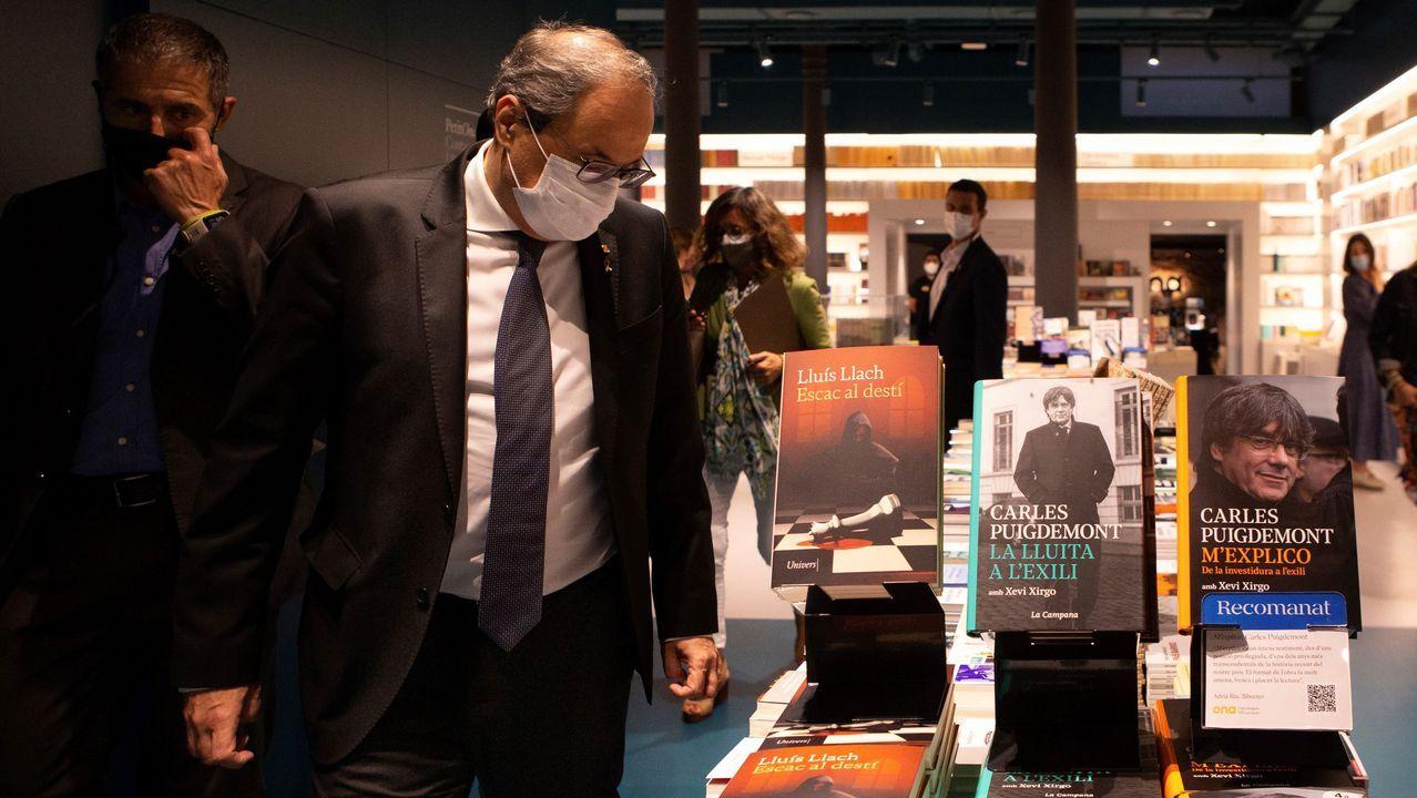 Quim Torra, este jueves, observa los libros publicados por el cantante Lluís Llach y por el prófugo de la Justicia Carles Puigdemont