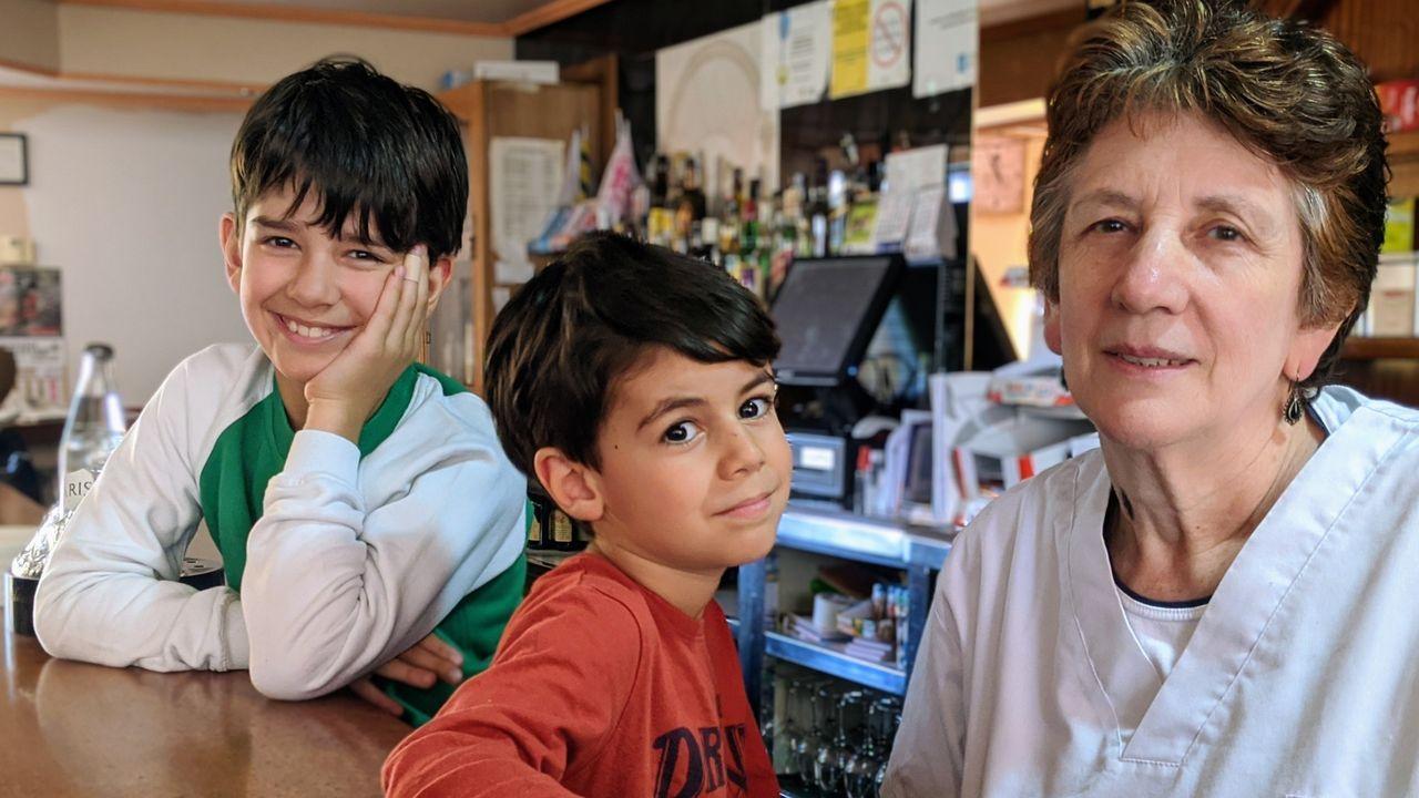 Playasen la provincia deA Coruña.Milucha y sus nietos, Xoel y Lois, detrás de la barra del bar al que ha dedicado buena parte de su vida