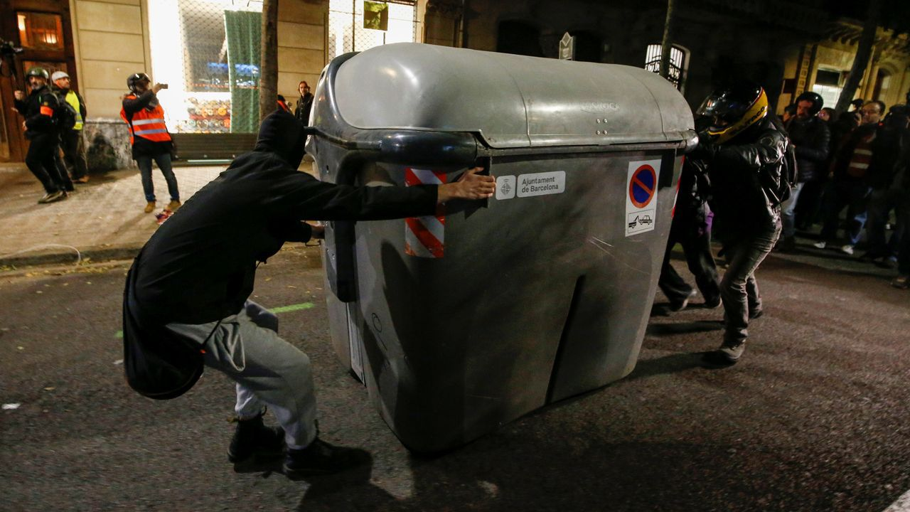 Varios manifestantes mueven un contenedor para utilizarlo de barricada, ayer en Barcelona