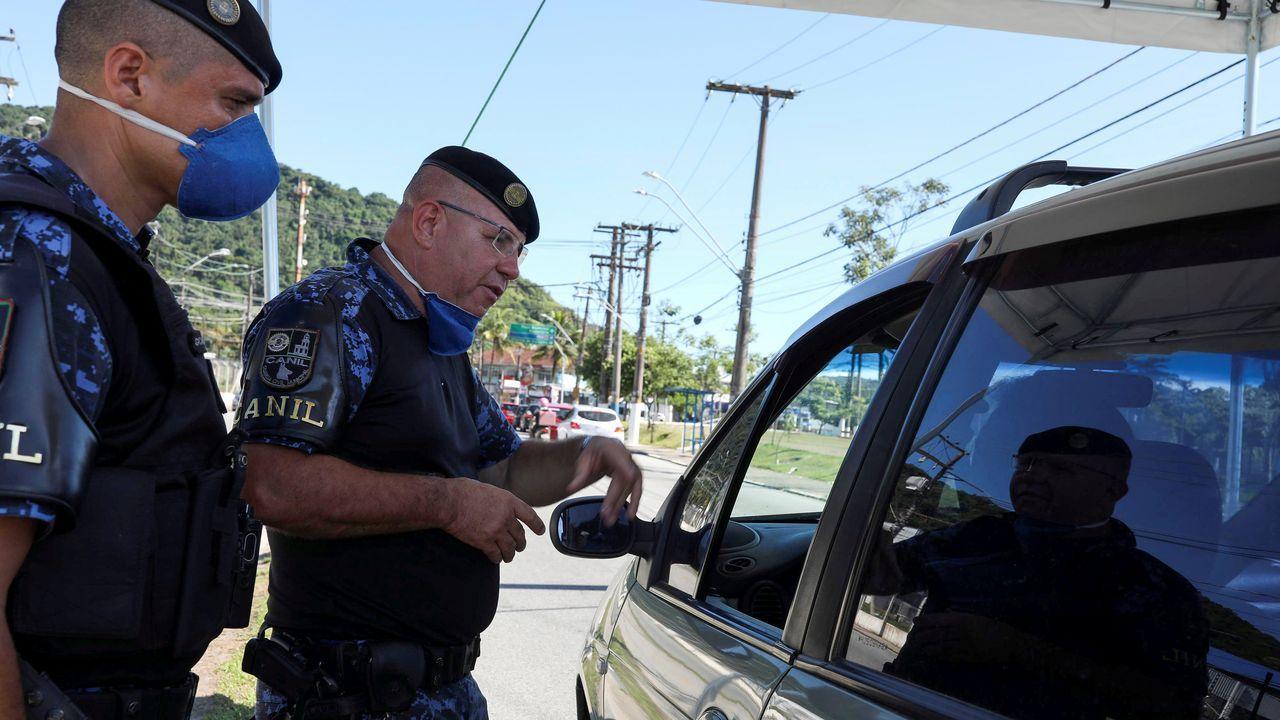 Oficiales de Policía registran a un viajero en la entrada de la ciudad, en medio de la crisis del coronavirus en Sao Paulo, Brasil