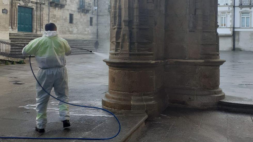 Un operario limpiando las pintadas en una de las columnas de entrada de la Catedral de Lugo