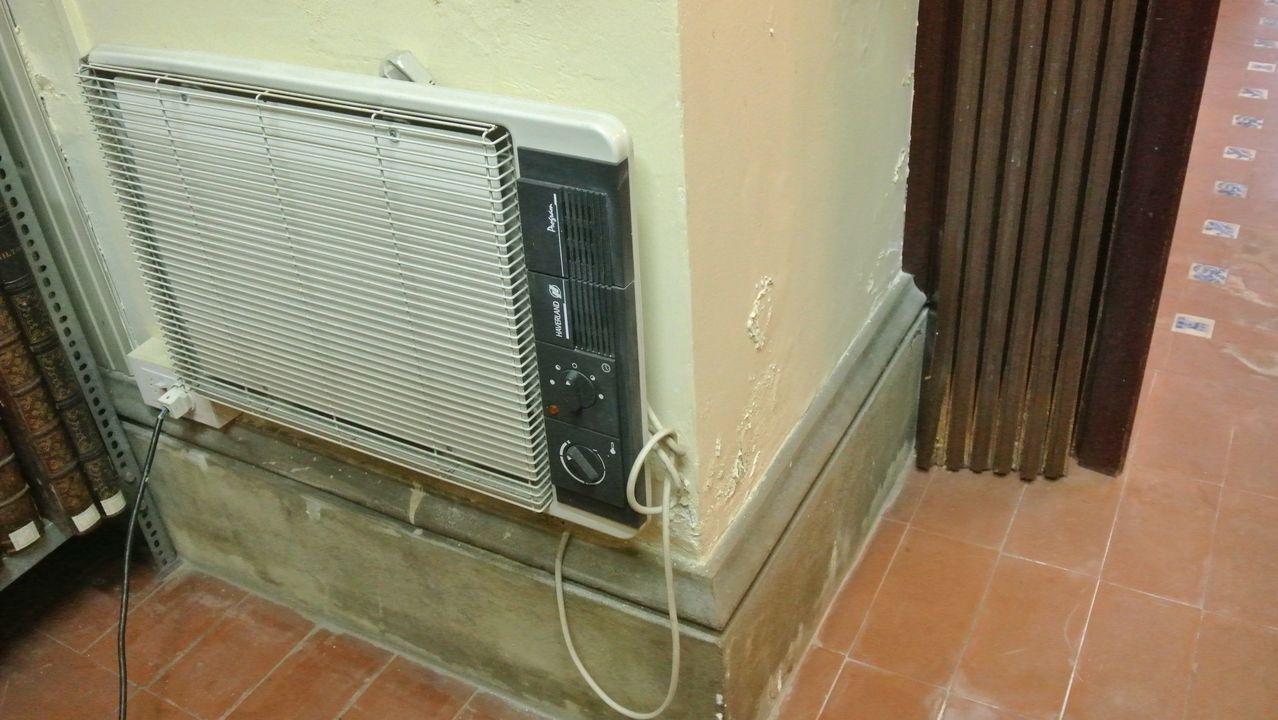 Un viejo radiador elétrico colgado de una pared dañada