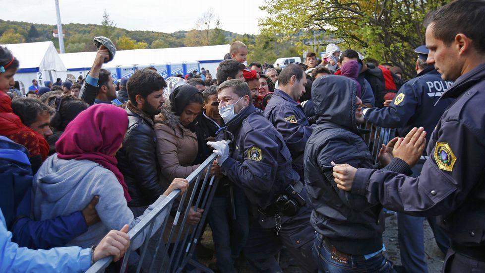 Un grupo de refugiados tratan de romper un cordón policial en  Sentilj, en la frontera de Eslovenia con Austria