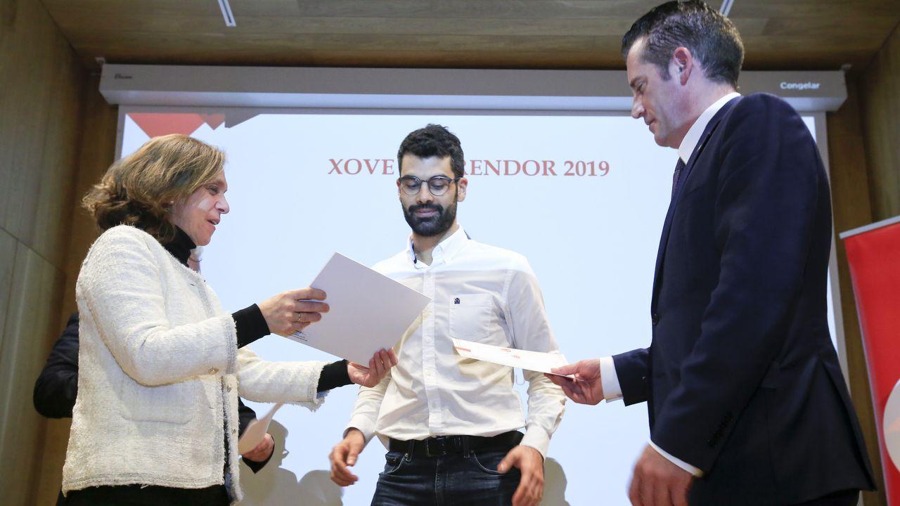 Primera feria de coches en Ribeira.El monfortino Daniel Rodríguez —centro— en el momento de recoger el premio AJE para los jóvenes emprendedores