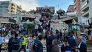 Ciudadanos y equipos de rescate buscan supervivientes en un edificio derruido en Esmirna
