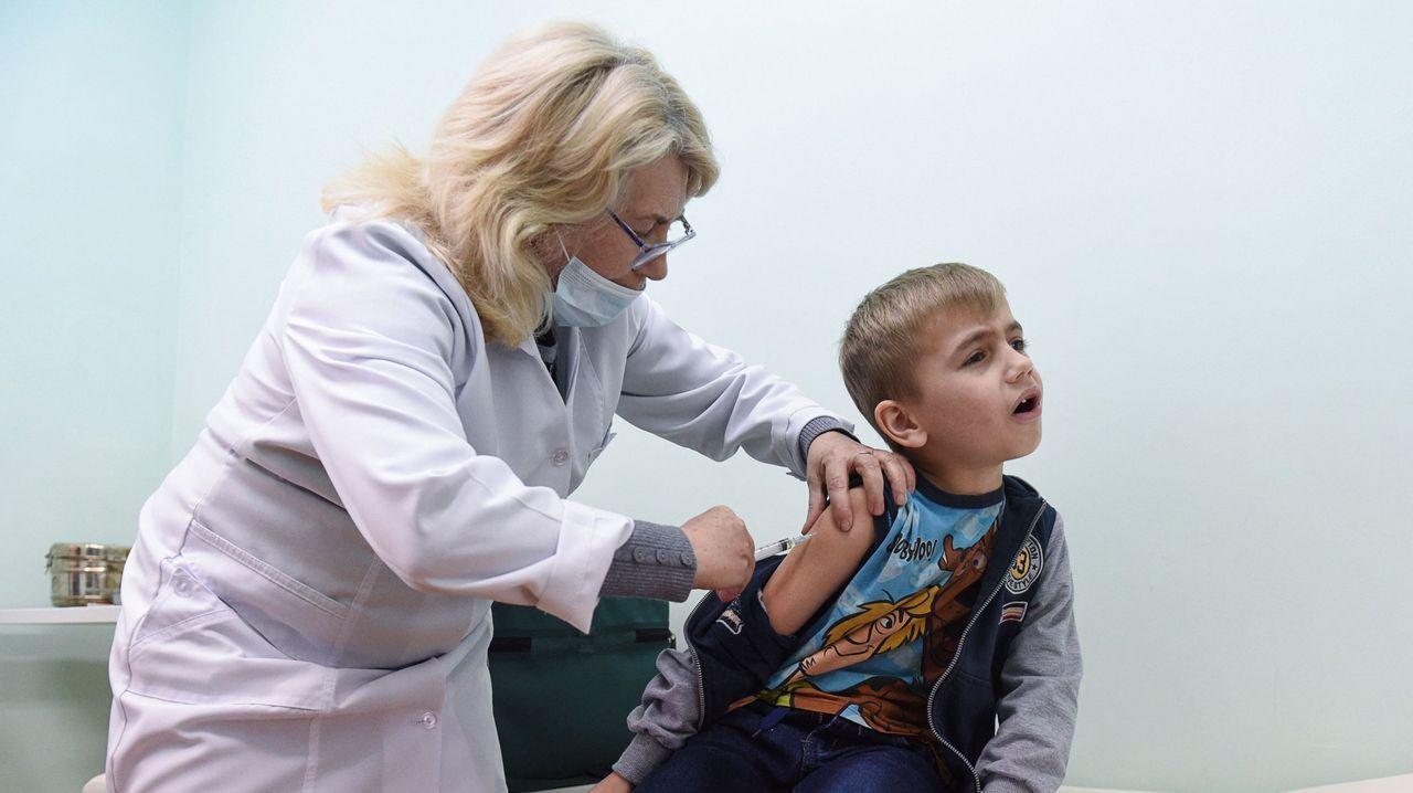 Contaminación en Gijón.Una sanitaria vacuna a un niño en Ucrania