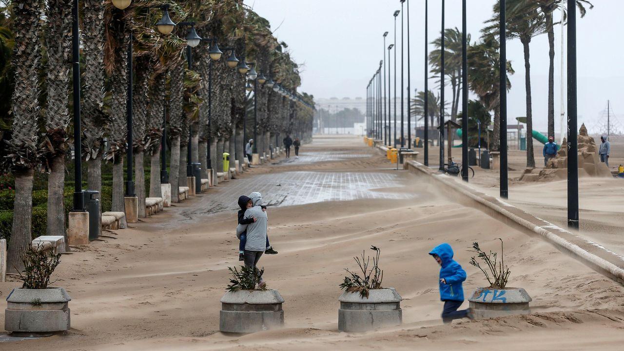 El paseo marítimo de Valencia ha quedado cubierto por la arena arrastrada por el fuerte viento desde la playa hacia el interior.